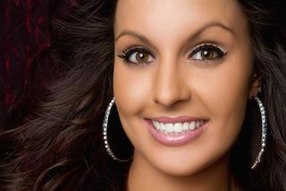 a woman smiles in front of a black backdrop | cosmetic dentist chattanooga