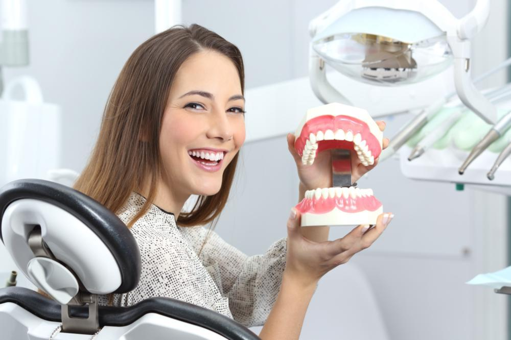a woman smiles and holds a dental model | root canals chattanooga