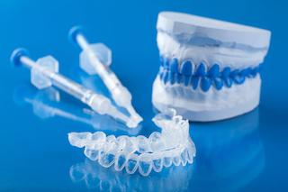 a set of whitening trays, gel and a mold on a blue table | east brainerd tn teeth whitening