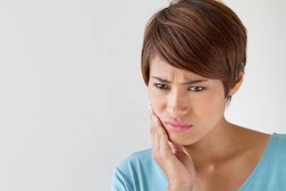 a woman holds her hand to her mouth | Chattanooga root canal dentist