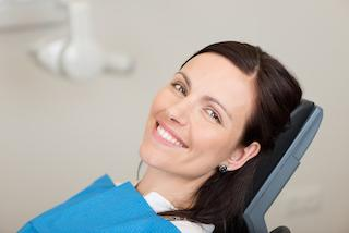a woman smiles in the dental chair | chattanooga periodontal treatment